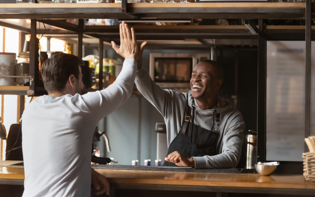 Two people hi-fiving at a bar