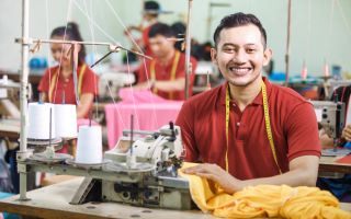 man sitting at a sewing machine looking at camera smiling
