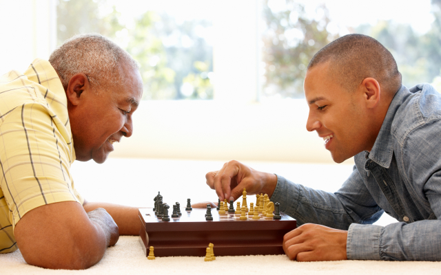 Elderly mand and a yonger man playing chess