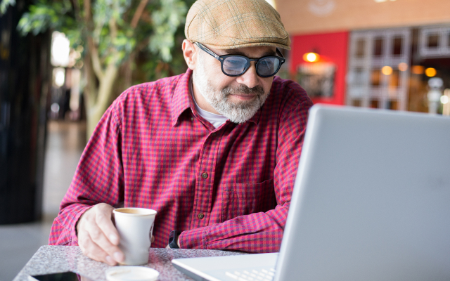 Older man in a coffe shop, looking at laptop screen