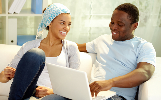 Man and woman looking at laptop screen and laughing