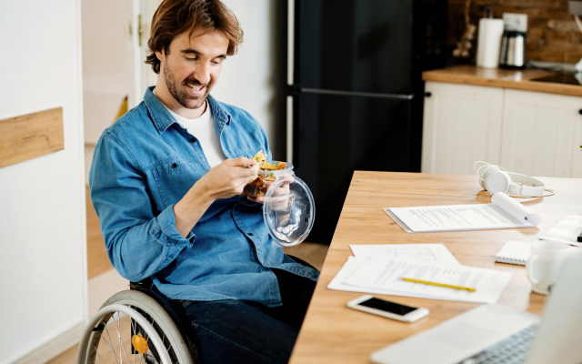 Man in wheelchair at kitchen table eating