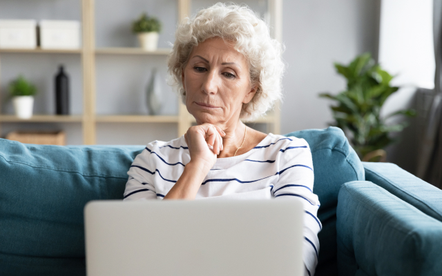 Older woman sitting and looking at laptop