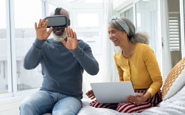 Man with virtual headset on and older woman sitting next to him