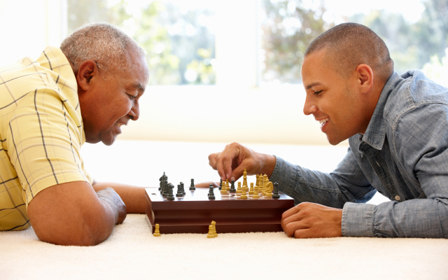 Elderly man and young man playing chess