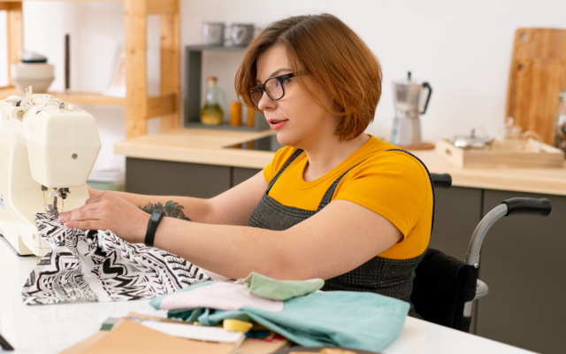 Woman sittling down using a sewing machine