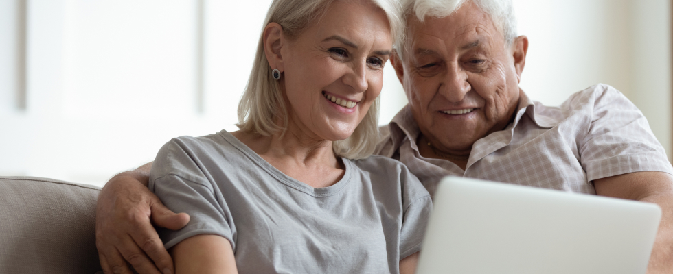 Elderly couple sitting down, looking at laptop